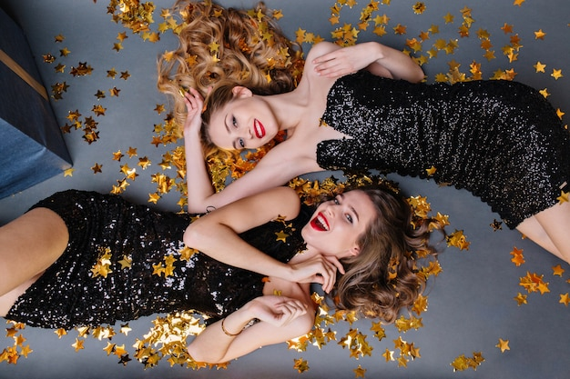 Portrait from above two fashionable young women laying in golden tinsels. luxury black dress, red lips, long curly hair, brightful mood, having fun, smiling, gorgeous models.