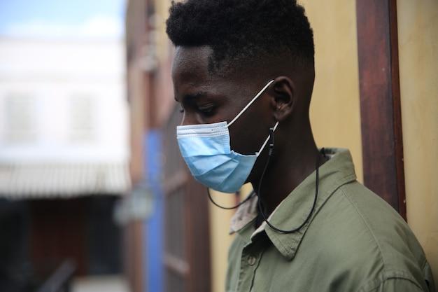 フェイスマスク保護を持つ若いアフリカ系アメリカ人男性の肖像画正面図