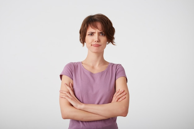 Portrait of frowning displeased short-haired lady in blank t-shirt, doubts the decision with arms crossed, stands over white wall.