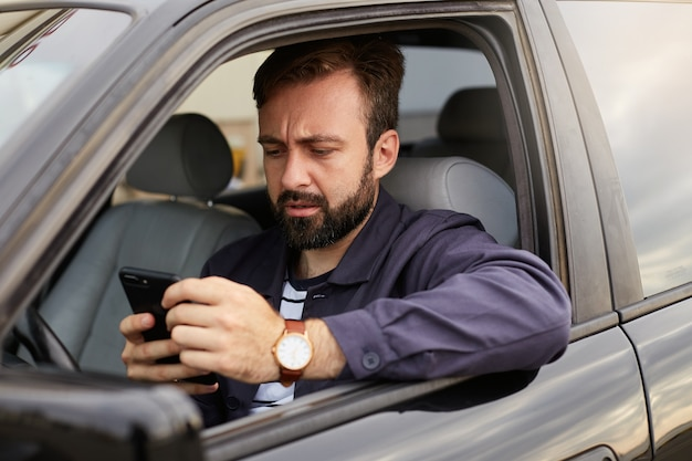 Portrait of frowning dosconected bearded man in a blue jacket and striped t-shirt, sits behind the wheel of the car, chatting with colleague by phone, displeased with the argument.