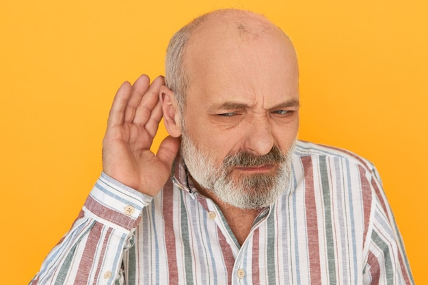 Portrait of frowning frustrated bearded male pensioner in striped shirt keeping hand at his ear, listening attentively, trying to hear indistinct talking. hearing problems and eavesdropping