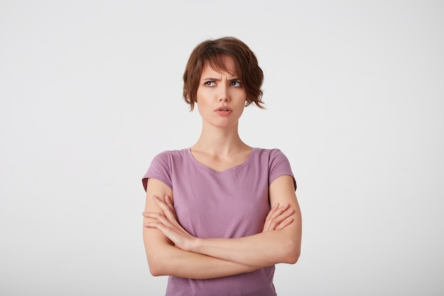 Portrait of frowning short-haired lady in blank t-shirt, trying to remember what offended her boyfriend, stands over white background with crossed arms.