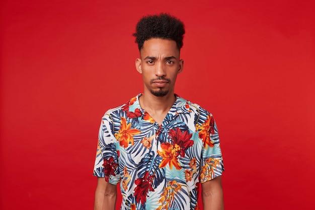 Ritratto di giovane ragazzo afroamericano accigliato, indossa in camicia hawaiana, guarda la telecamera con espressione infelice, si erge su sfondo rosso.