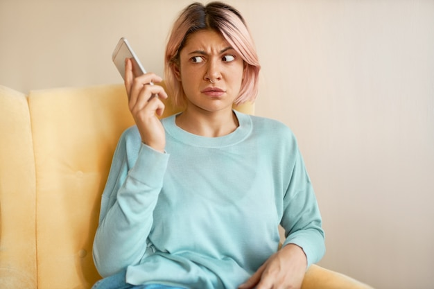 Portrait of frowning young woman in blue sweatshirt holding mobile, dialing wrong number, having shocked look.
