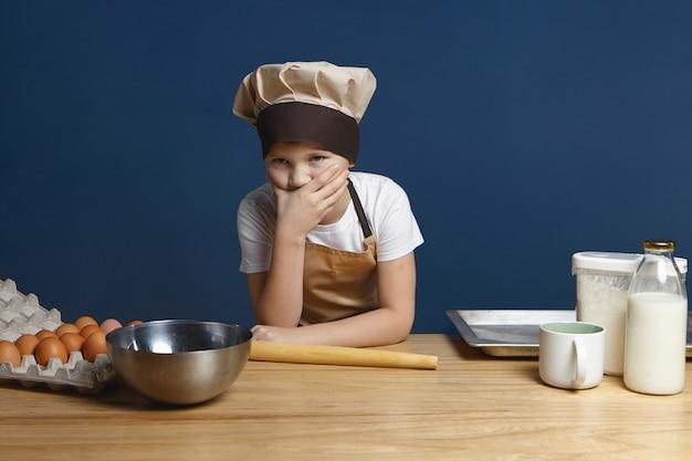 Ritratto di ragazzo frustrato di 10 anni in uniforme da chef che copre la bocca sentendosi perplesso mentre prepara frittelle da solo per la prima volta con il latte