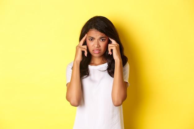Ritratto di frustrata ragazza afro-americana, accigliata e toccando la testa, guardando la telecamera in difficoltà, in piedi su sfondo giallo.
