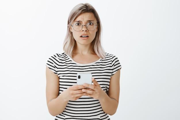 Ritratto di ragazza bionda frustrata in posa in studio con il suo telefono