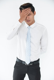 Portrait of frustrated businessman covering face