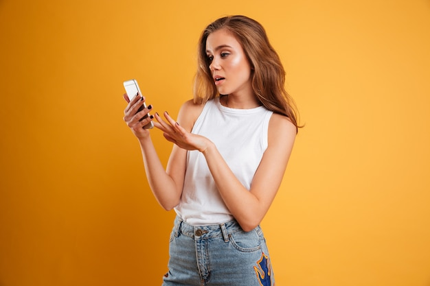 Portrait of a frustrated confused girl looking at mobile phone