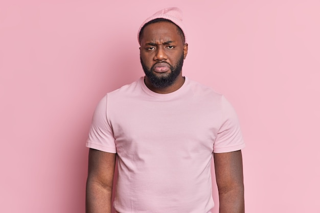 Portrait of frustrated displeased bearded man looks unhappily at camera being dissatisfied with something wears hat and casual t shirt isolated over rosy wall