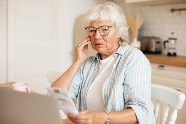 Portrait of frustrated gray haired female pensioner wearing eyeglasses sitting at kitchen table with laptop, holding bill and touching face, shocked with amount of total sum for electricity