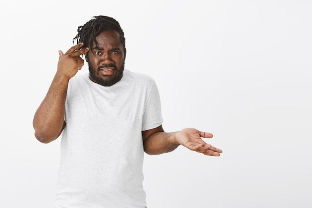 Ritratto di ragazzo frustrato con trecce in posa contro il muro bianco