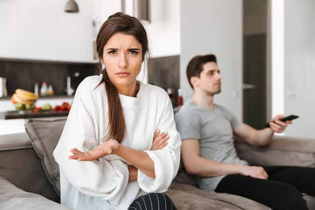Portrait of a frustrated young woman sitting with her boyfriend