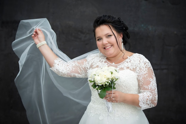 Portrait of a full bride with a waving veil with a bouquet on a dark background.