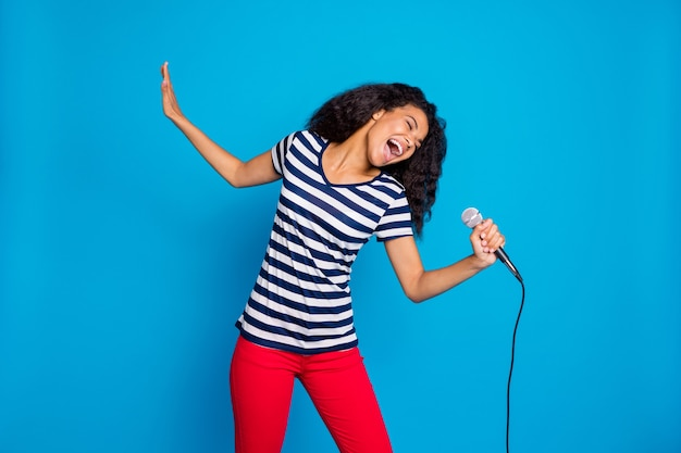 Portrait of funky afro american woman hold microphone sing song perform stage