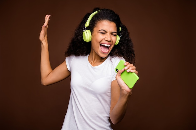 Portrait of funky afro american youth imagine she perform rock concert sing song use smartphone mic listen music on green wireless headset wear white t-shirt.