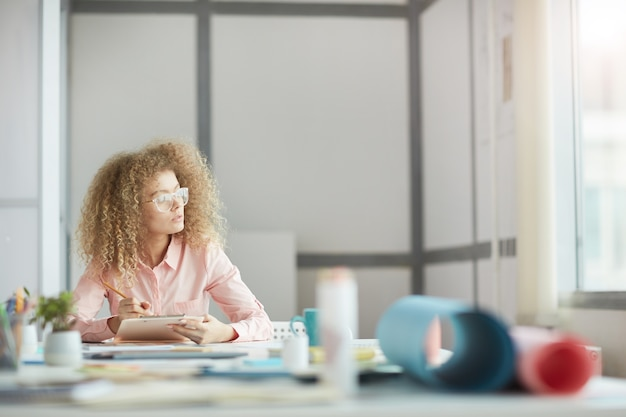 Portrait of funky young businesswoman wearing glasses looking at window while daydreaming at workplace, copy space