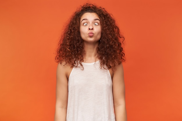 Portrait of funny, adult redhead girl with curly hair. wearing white off-shoulder blouse. squinting her eyes and making silly face. isolated over orange wall
