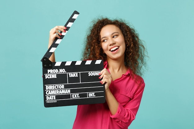 Portrait of funny african girl in casual clothes holding classic black film making clapperboard isolated on blue turquoise background. people sincere emotions lifestyle concept. mock up copy space.