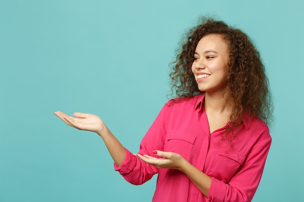 Portrait of funny african girl in pink casual clothes looking pointing hands aside isolated on blue turquoise wall background in studio. people sincere emotions, lifestyle concept. mock up copy space.