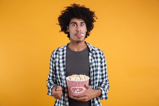 Portrait of a funny afro american man eating popcorn