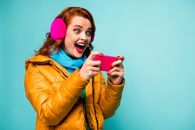 Portrait of funny amazed lady hold telephone addicted video games player open mouth excited wear trendy casual ear covers yellow overcoat scarf.