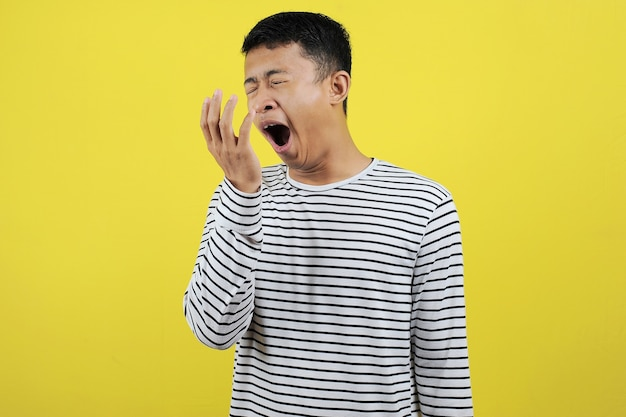 Portrait of funny asian man yawning covering open mouth and showing a sleepy gesture. feeling being tired from hard work, isolated on yellow background