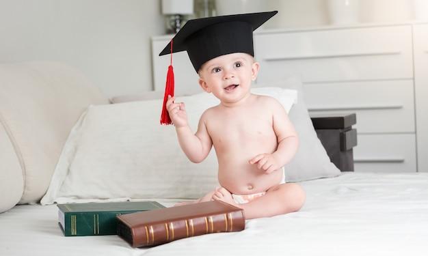 Portrait of funny baby boy in diapers wearing black graduation cap