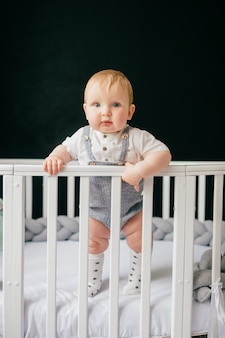 Portrait of funny baby standing in crib.