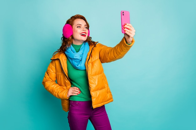 Portrait of funny beautiful lady hold telephone hands taking selfies wear trendy casual ear covers yellow overcoat scarf magenta pants jumper.