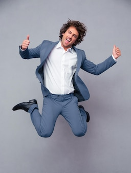 Portrait of a funny businessman jumping and showing thumbs up isolated on a white wall
