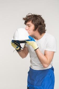 Portrait of funny caucasian male builder kissing helmet on white background.
