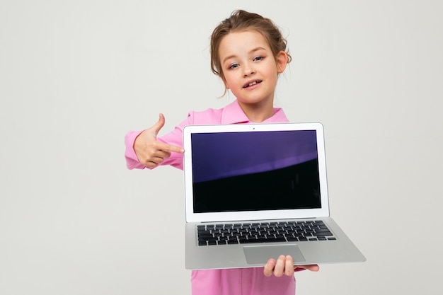 Portrait of funny charming baby in pink costume showing laptop