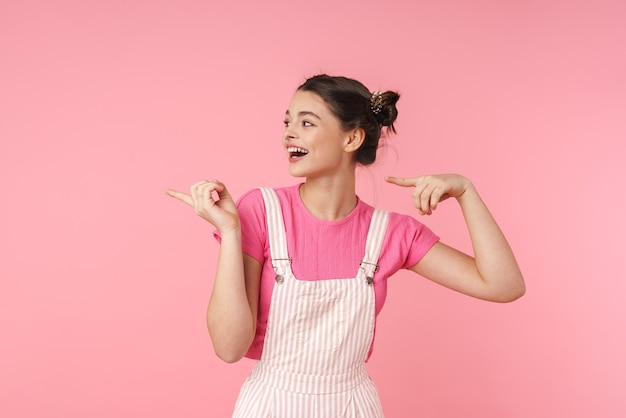 Portrait of funny charming girl with nose ring pointing fingers aside and laughing isolated over pink wall