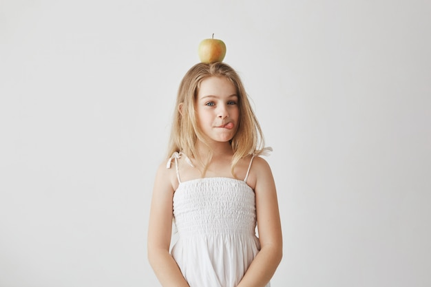 Portrait of funny cheerful girl with blond hair in white dress holding apple on head, showing tongue, making silly expressions.