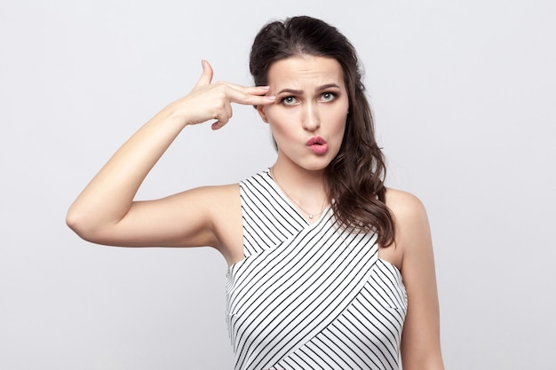 Portrait of funny crazy beautiful young brunette woman with makeup and striped dress standing with pistol gesture and looking away. indoor studio shot, isolated on grey background.
