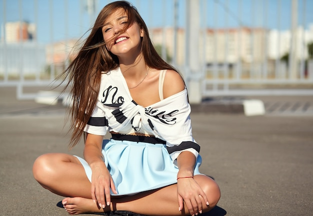 Portrait of funny crazy glamor stylish smiling beautiful young woman model in bright hipster summer casual clothes posing in the street on asphalt