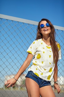 Portrait of funny crazy glamor stylish smiling beautiful young woman model in bright hipster summer casual clothes posing in the street behind iron grating and blue sky