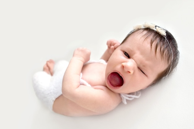 Portrait of funny crying newborn baby. emotions of discontent. colic. selective focus