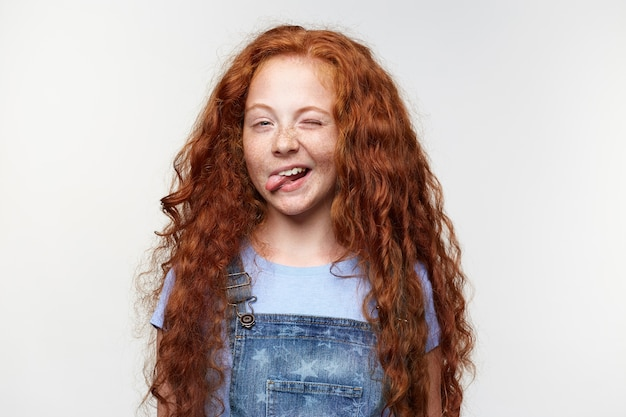 Portrait of funny cute freckles little girl with ginger hair, winks and shows tongue at the camera, stands over white background.