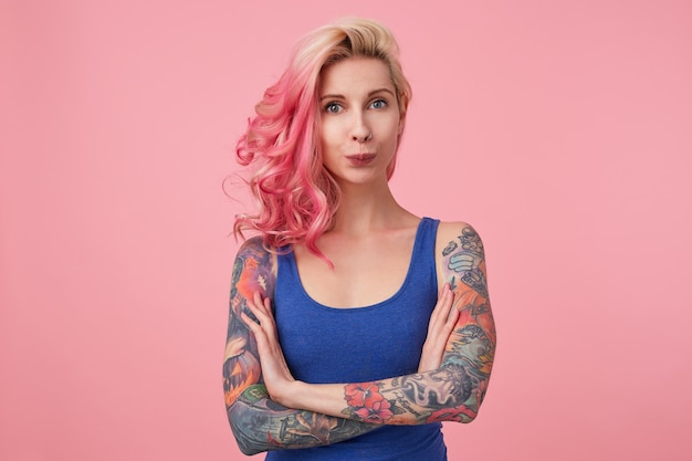 Portrait of funny cute lady with pink hair and tattooed hands, standing and looking, wearing a blue shirt. people and emotion concept.