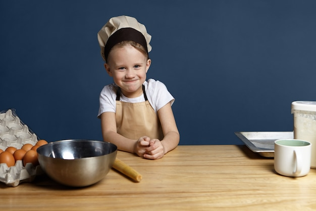 Portrait of funny cute little boy wearing beige apron and chef cap standing in kitchen with metal bowl cup, tray, eggs and flour on table, ready to make dough for homemade bread pie or cake copy space