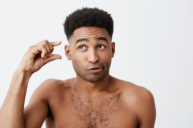 Portrait of funny dark-skinned american guy with curly hair and without clothes looking aside with silly and cynic expression, gesticulating with hand. people's emotions.