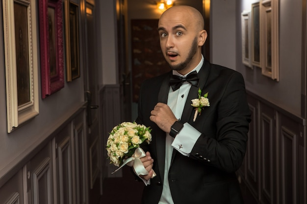 Portrait of funny elegant bridegroom with a bouquet in hands