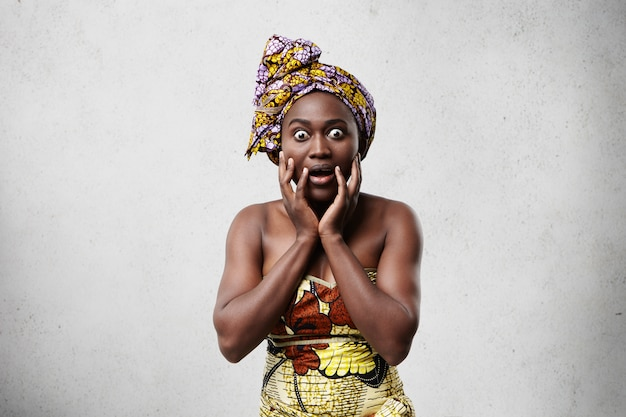 Ritratto di donna nera stupita emotiva divertente in abiti luminosi tenendo le mani sul viso, stupita con pettegolezzi o grandi prezzi di vendita. espressioni facciali umane, emozioni, sentimenti e atteggiamento