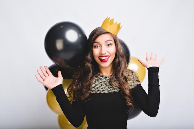 Портрет смешной взволнованной девушки празднует новый год с золотыми и черными шарами