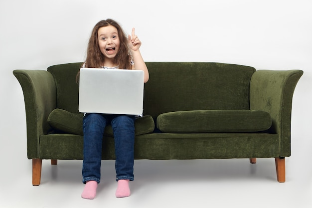 Portrait of funny excited little girl in jeans sitting on sofa with portable computer on lap, exclaiming excitedly and raising finger.