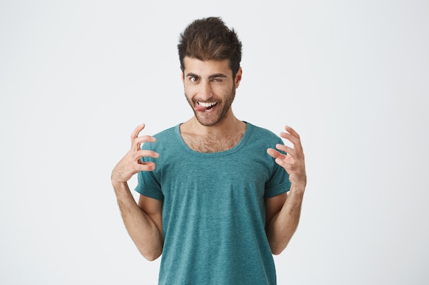 Portrait of funny expressive spanish guy in blue t-shirt, playing fool showing tongue and teeth, having fun indoors. human face expressions.