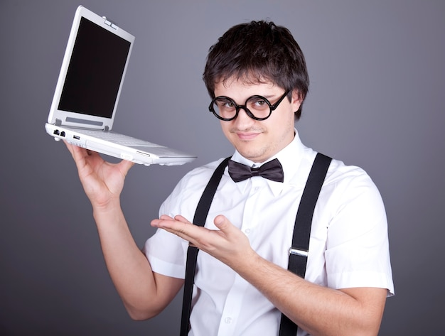 Portrait of funny fashion men in suspender with bow tie and glasses keeping notebook.