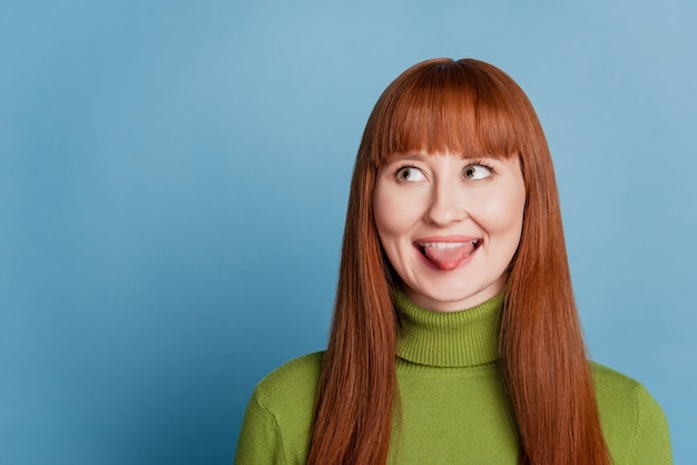 Portrait of funny girl look copyspace show tongue on blue background